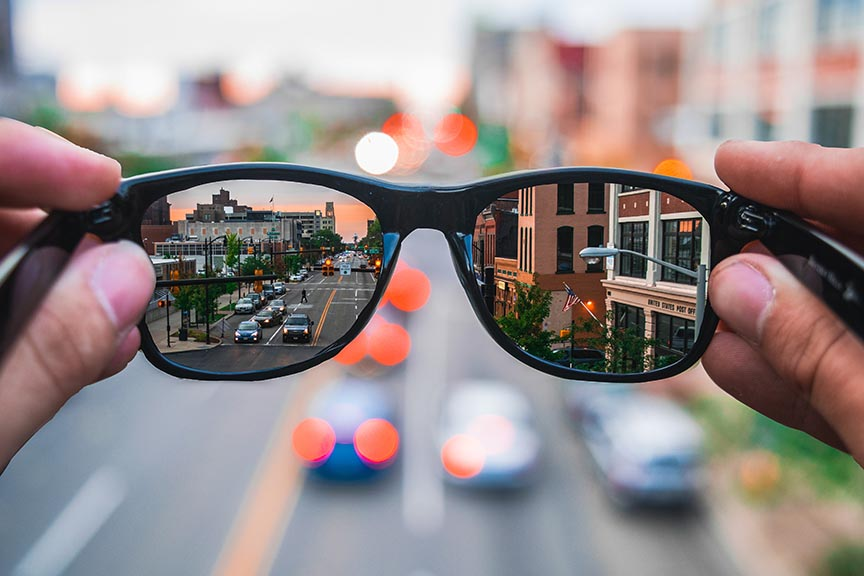 Blurry background with clear sunglasses with city reflection